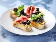 Bruschetta s olivovou pomazánkou, černými olivami v rozmarýnu a mortadelou